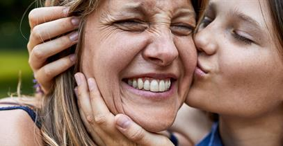 daughter-kissing-mother-on-cheek