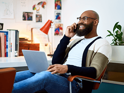 man-smilining-on-cell-phone-on-home-office